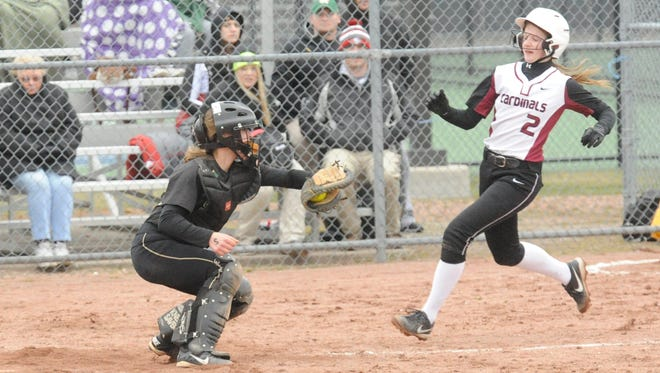 Fond du Lac's Megan Elford (2) looks for a way around Oshkosh North catcher Sammy Buerger in the third inning of Tuesday's Fox Valley Association softball game in Oshkosh.