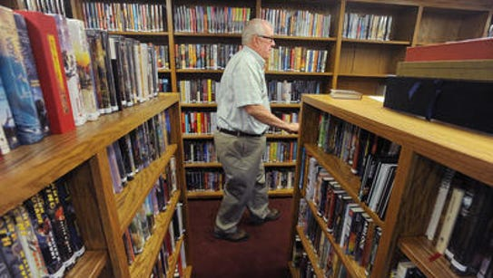 The Rev. Allen Lewis walks among his book collection.