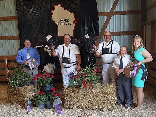 District 6 Grand Champion and Reserve Grand Champion of the Open Show (from left) Associate Judge Mike Duckett, Reserve Grand Champion Rock-N-Hill-II Phoeni Cosmo, Chris McCullough , Grand Champion Glenn-Ann Gold Chip Shiraz, exhibited by Glenn-Ann Holsteins, Brian Behnke, Judge Norm Nabholz, 2017 WHA Princess Attendant Kelsey Cramer.