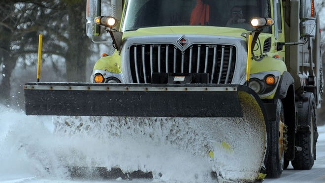 A Marion County snowplow makes its way along Marion-Cardington Road to clear drifting snow.