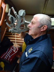 Crew member Bob Nash practices with his sextant, for