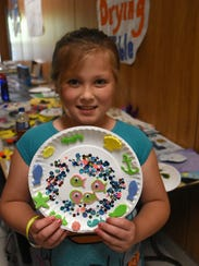 Devin Wood, 8, displays the project she made at Camp