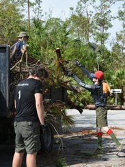 Scouts load a truck with branches. Boy Scout Troop