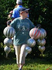 Alice Rizzo grabs some massive ornaments.  Workers