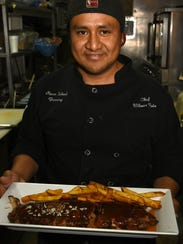 Chef Wilmer Ruiz with a rack of MIB ribs. The Marco