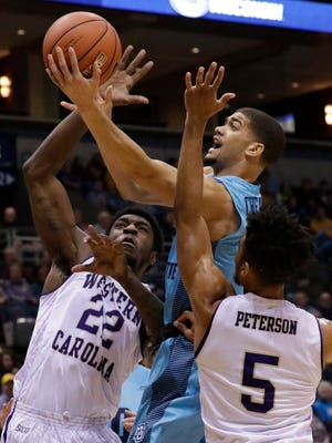 Marquette's Haanif Cheatham shoots between Western Carolina's Jesse Deloach  and Devin Peterson.