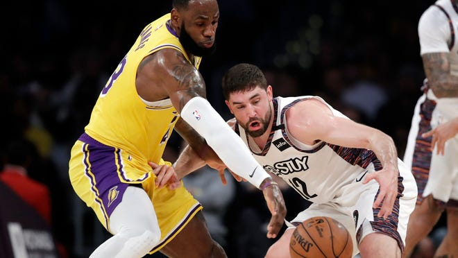 Los Angeles Lakers' LeBron James, left, strips the ball from Brooklyn Nets' Joe Harris during the first half of an NBA basketball game Tuesday, March 10, 2020, in Los Angeles.