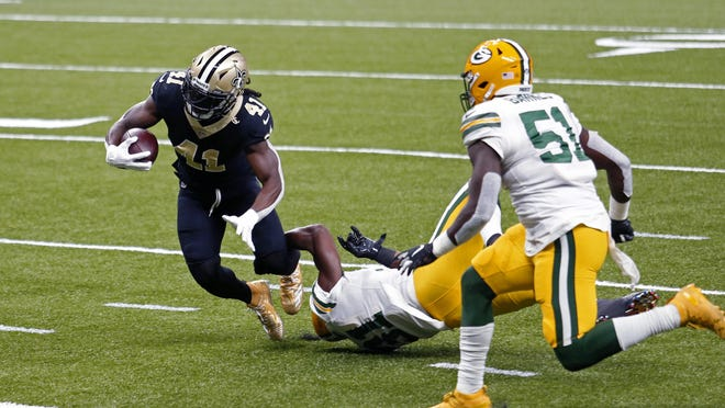 Dean Lowry and the Green Bay Packers had trouble stopping Saints running back Alvin Kamara (41) much of the day in New Orleans, Sunday, but they still hung on for a 37-30 win.