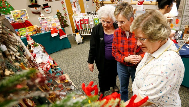 Judy Lown, left, Sharon Joralemon, and Donna Cloes check out an array of holiday decorations Wednesday at the Arnot Ogden Medical Center Auxiliary's Holiday Extravaganza.