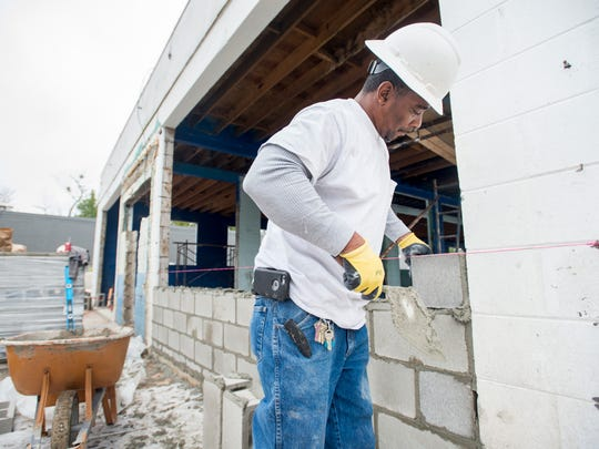 Emerald Coast Constructors employees work Wednesday, Dec. 27, 2017, to convert the old Garden Street Car Wash into the new Live! Juice Bar & Music Venue in Pensacola.