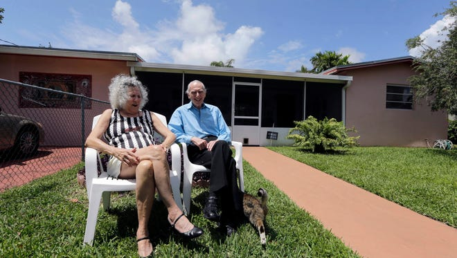 In this May 11, 2015 photo, Al Karp, right, and wife Saundra, pose in front of their home in North Miami Beach, Fla. The Karps, along with their son, Larry, perform old standards locally as the Karp Family band to ease stress and help raise money to save their home from foreclosure. (AP Photo/Alan Diaz)