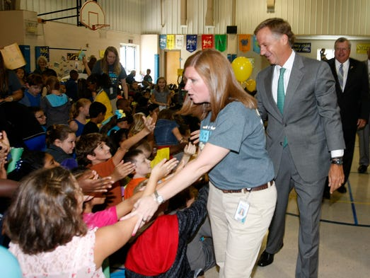 Hazelwood Elementary Principal Jessica Harris, left, Tenn. Gov. Bill Haslam slap hands with students during a pep rally Thursday morning. State Rep. Curtis Johnson, right, follows behind. The Clarksville school is one of four in the local district to make the state's list of top TCAP performers.