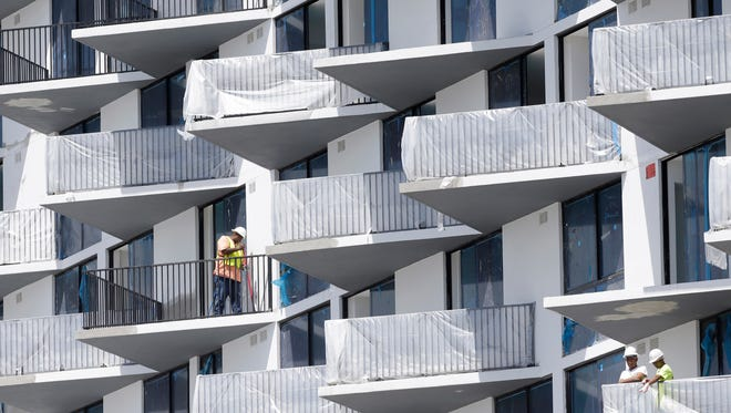 In this Monday, Aug. 17, 2015 photo, construction workers work at the site of a high-rise condominium as part of the downtown Doral complex developed by the Codina Partners in Doral, Fla.