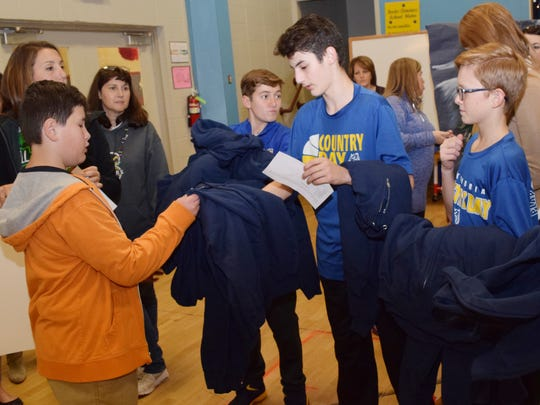 Jamal Farhat (center) and Jacob Bareswill (right), both seventh-graders at Alexandria Country Day School, hand out jackets to Mabel Brasher Elementary School students including fifth-grader Colin Bratton (left).
