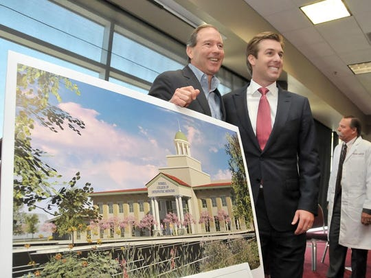 Daniel C. Burrell, board chairman of the Burrell College of Osteopathic Medicine, and U.S. Sen. Tom Udall, D-N.M., left, stand next to a rendering of the new medical school being built on the New Mexico State University campus.