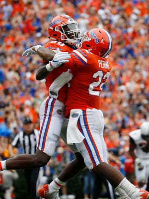 Florida Gators running back Lamical Perine (22) is congratulated by tight end C'yontai Lewis (80)  as he scores a touchdown against the Vanderbilt Commodores during the first half at Ben Hill Griffin Stadium.