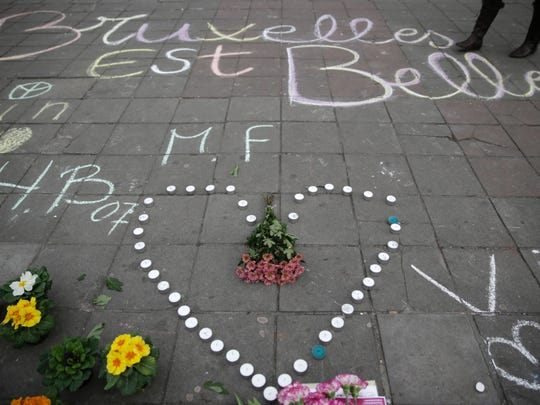 """A message written on the ground reads """"Brussels is beautiful"""" next to flowers and candles following attacks in Brussels on March 22, 2016."""