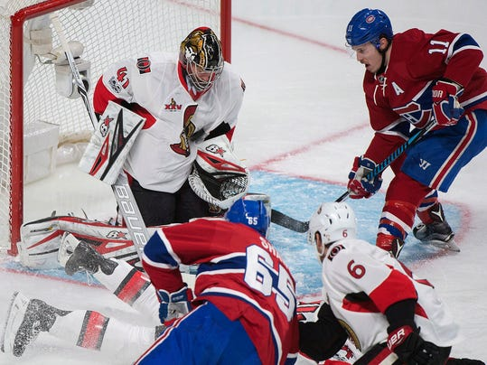 Montreal Canadiens' Brendan Gallagher (11) moves in on Ottawa Senators goaltender Craig Anderson as Senators' Chris Wideman (6) battles with Canadiens' Andrew Shaw (65) during the first period of an NHL hockey game in Montreal, Sunday, March 19, 2017. (Graham Hughes/The Canadian Press via AP)