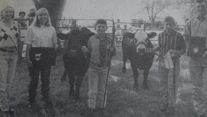 Jonathon Davis, center, was named the grand champion, and Stephen Hendrickson, second from right, the reserve grand champion at the UC 4-H Steer Show in July 1997. Also pictured are (from left) Fair Queen Jona Schermerhorn, ringmaster Carrie Stenger, and judge Nathan Pike.