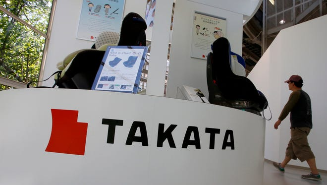 In this Wednesday, May 4, 2016 photo, a visitor walks past child seats, manufactured by Takata Corp., displayed at an automaker's showroom in Tokyo. Two people in Malaysia have died in recent traffic crashes in which Takata air bag inflators exploded with too much force, but authorities have yet to determine the exact cause of either death. Both crashes involved driver's air bag inflators in older Honda City small cars, according to a statement released Wednesday by Honda. The automaker says cars in both crashes were under recall to fix faulty Takata inflators, but repairs had not been made. (AP Photo/Shizuo Kambayashi)
