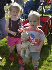 Nora LeBlanc, 3, left, and Isaac LeBlanc, 2, both of Westford hold American flags as they wait for the annual East Charlotte Tractor Parade to begin on Sunday, Oct. 8, 2017.