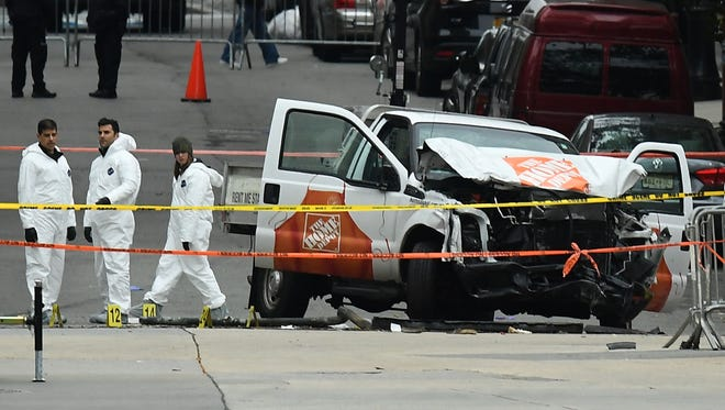 Investigators work around the wreckage of a Home Depot pickup truck a day after it was used in a terror attack in New York, the first to kill anyone since the 9/11 attacks.