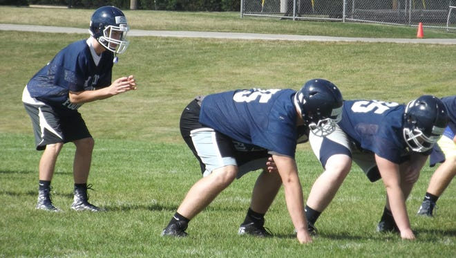 Bay Port senior Andrew Slick prepares to take a snap at practice Tuesday in Suamico in front of senior right tackle Cole Van Lanen.