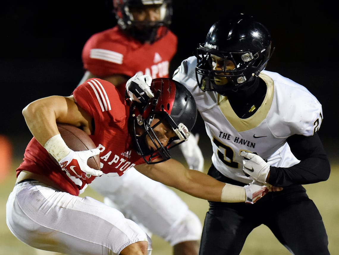 Ravenwood's Chris Rowland (23) is brought down by Whitehaven cornerback Deniro Tillman (21) after returning a punt during the second half of an 6A semifinal playoff football game at Ravenwood High School on Friday, Nov. 27, 2015 in Brentwood, Tenn. Ravenwood won 20-13.