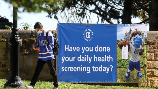A student walks past a banner on the Salve Regina campus on Tuesday morning.