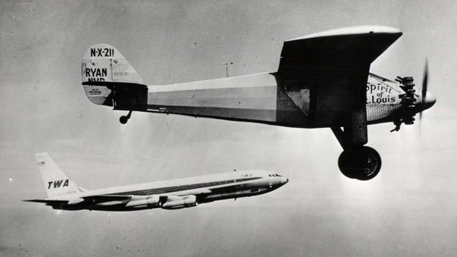 A TWA airplane flies alongside an exact replica of Charles Lindbergh's Spirit of St. Louis in an undated photo.