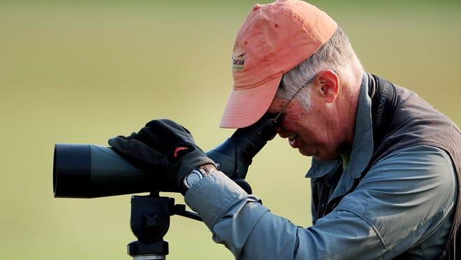 Tim Johnson, of Salem, looks through a scope during a Salem Audubon Society field trip at Ankeny National Wildlife Refuge, on Sunday near Jefferson.