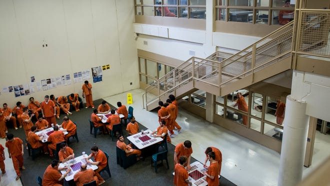 Inmates play card games and talk in the male pod at the St. Clair County jail.