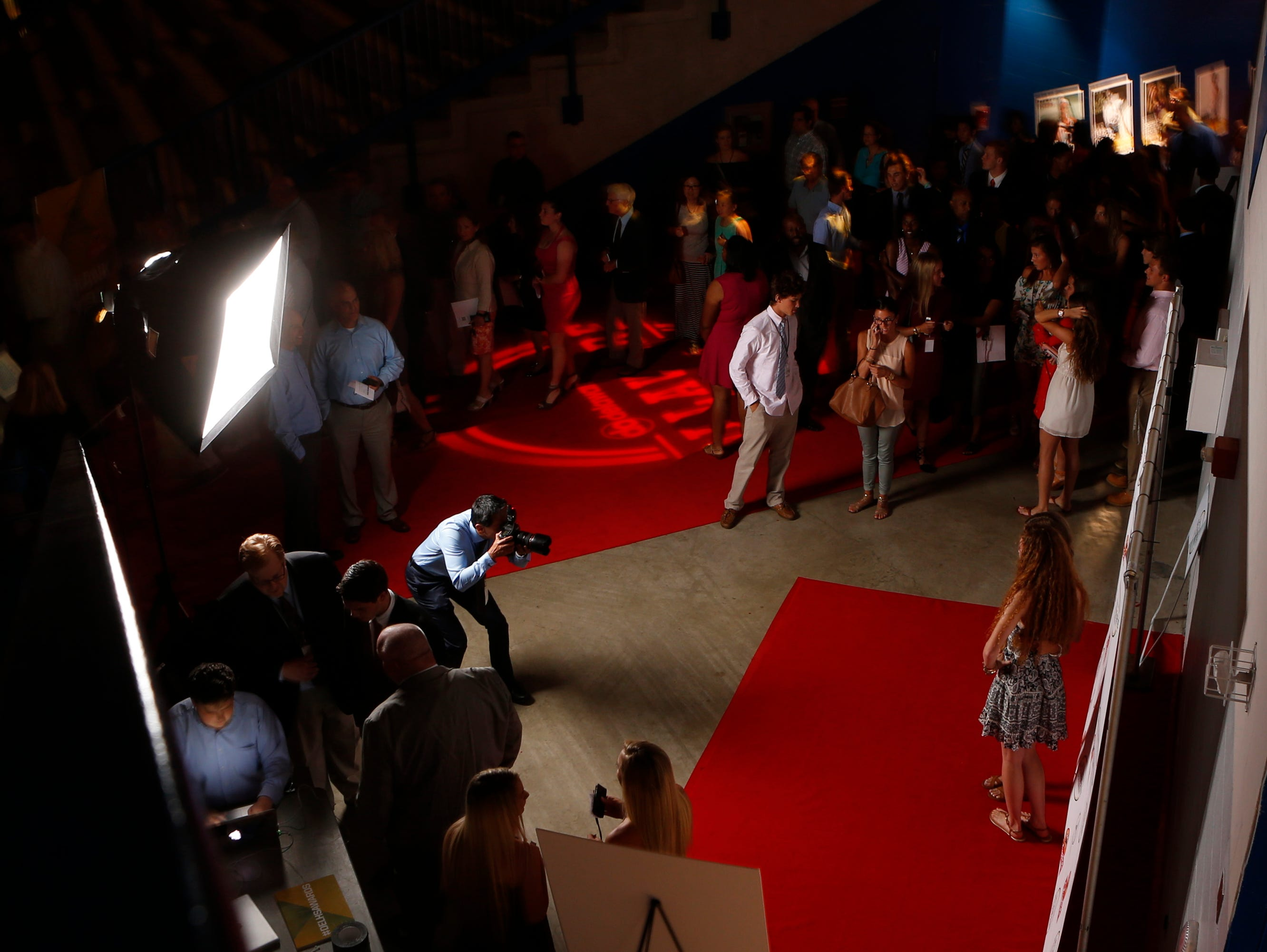 Attendees have their photos taken on the red carpet as they arrive during the Delaware Sports Awards banquet at the Bob Carpenter Center Wednesday.