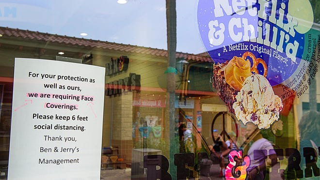 A sign beside the entrance informs patrons that face masks are required to enter Ben & Jerry's ice cream store on St. George Street in St. Augustine on Wednesday.