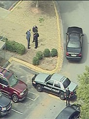 Law enforcement officials remain at the scene of a