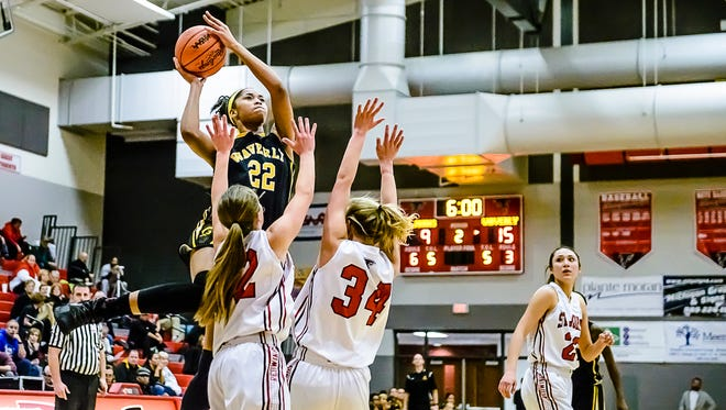 Alisia Smith ,22, of Waverly takes the ball to the basket over two St. Johns defenders during their game Friday January 27, 2017 in St. Johns.  KEVIN W. FOWLER PHOTO