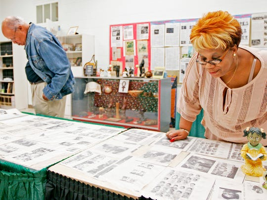 Nita Bellamy looks over yearbook photos from Rosenwald