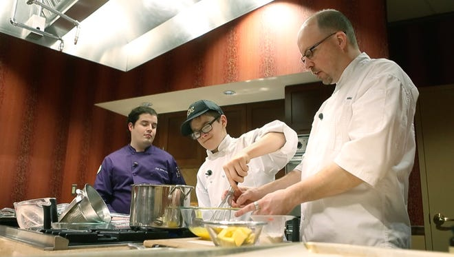 Wyatt Cheatle, 12, of Brighton whisks eggs following instructions from Wegmans executive chef Mark Makovec and, left, New York City pastry chef Steven Ciccione at Pittsford Wegmans in 2015.