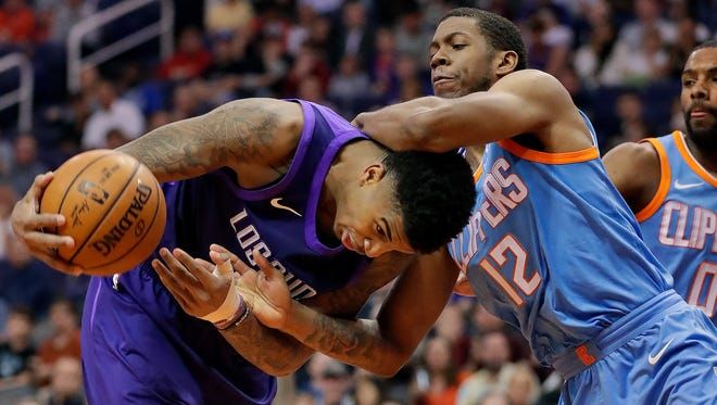 Phoenix Suns forward Marquese Chriss (0) is fouled by LA Clippers guard Tyrone Wallace (12) during the second half of an NBA basketball game Wednesday, March 28, 2018, in Phoenix.