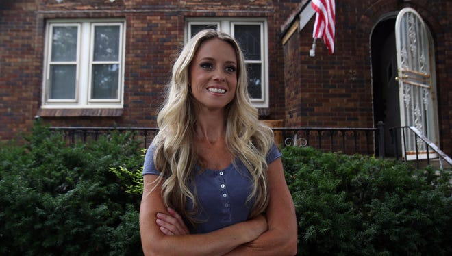 "Nicole Curtis of ""Rehab Addict"" stands July 23, 2013, in front of a Detroit home that she was rehabbing for the show."