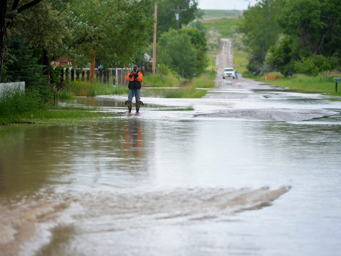 Flood water crosses Sun River-Cascade Road in the town