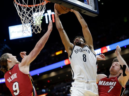Brooklyn Nets' Spencer Dinwiddie (8) shoots between Miami Heat's Kelly Olynyk (9) and Goran Dragic (7) during the first half of an NBA basketball game Friday, Dec. 29, 2017, in Miami. (AP Photo/Lynne Sladky)