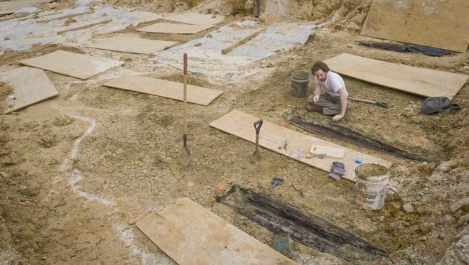 In this 2013 UMMC photo, Forrest Follet from the Cobb Institute of Archaeology, Mississippi State University, removes the soil from the lids of the dozens of unmarked graves uncovered during construction on the UMMC campus.