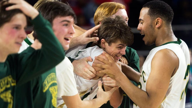 Catholic's Luke Smith, center, is congratulated by teammates after his game-winning shot against Whites Creek in a Class AA semifinal game Friday at Middle Tennessee State University in Murfreesboro.