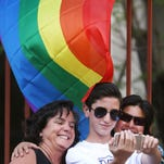 Married couple Irene Estrada, obscured at rear right, and Michelle McLoughlin, left, squeeze in with son, Logan McLoughlin, 11, for a selfie in front of a rainbow flag as they celebrate after the Supreme Court declared that same-sex couples have a right to marry anywhere in the United States, in Tucson, Arizona, Friday.