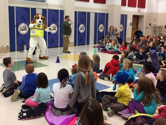 York County Literacy Council conducted assemblies in schools to promote reading and its Buck A Book program. The presentations included Digger Dog, who teaches natural gas safety issues for Columbia Gas. Pictured are Russell Bedell, of Columbia Gas, and Digger Dog with students at Charles B. Wallace Elementary School.