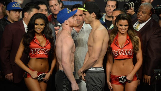 Canelo Alvarez (left) and Julio Cesar Chavez Jr. pose for a photo after weighing in for their upcoming bout at MGM Grand Garden Arena.