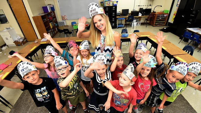 Carrie Horton and her Norfork Elementary School first graders give a big wave Monday during the first day of school.