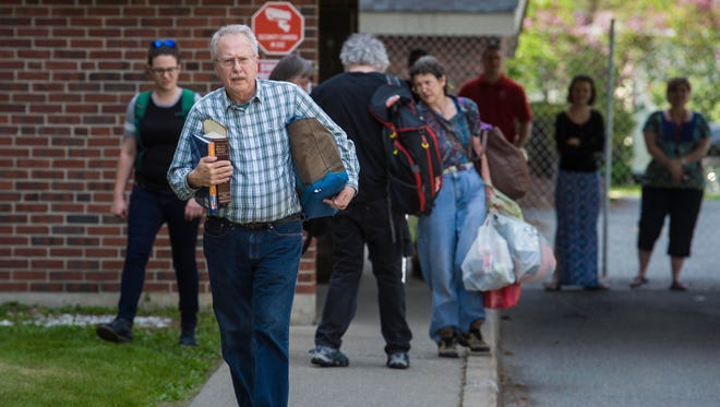 Burlington College teacher Grant Crutchfield carries some belongings as he leaves the school on Friday, May 20, 2016.