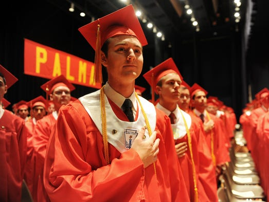 Grads pledge allegiance to the flag at Sunday's 60th Palma High School commencement exercises at Sherwood Hall in Salinas.